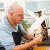 senior electrician examining a ciruit board