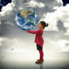 Child holding the world in her hands - Future and happiness concept